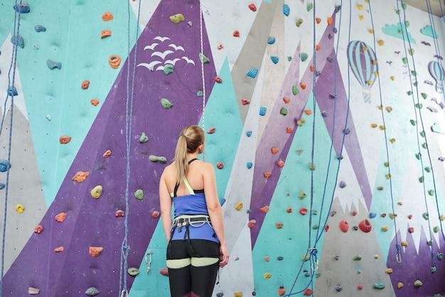 Widok z tyłu młodej samicy wspinaczki stojącej przed ścianą wspinaczkową ze skałami i patrząc na zdjęcia podczas przygotowań do treningu