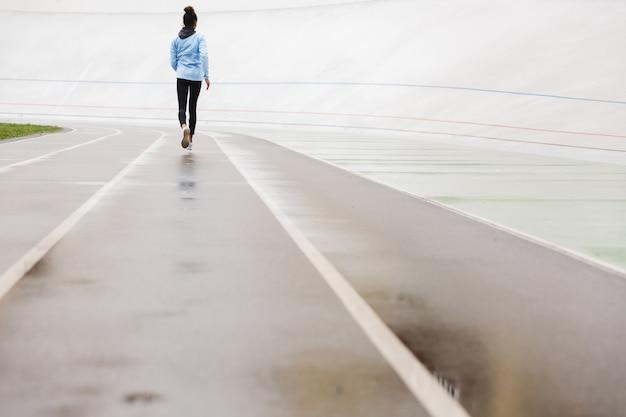 Widok z tyłu młodej sprawnej afrykańskiej sportsmenki biegającej na stadionie