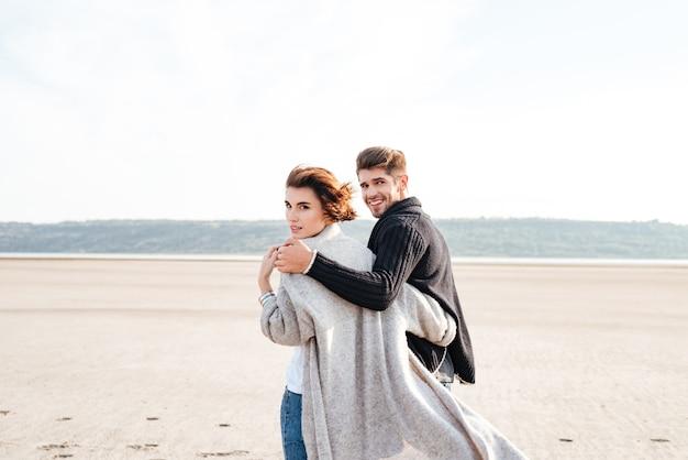 Widok z tyłu młodej uśmiechniętej pary przytulającej się i patrzącej na kamerę na plaży