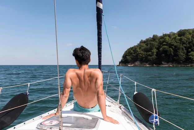 Widok z tyłu młody człowiek korzystających z wakacji na łodzi