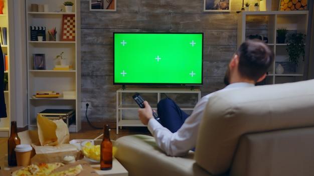 Widok z tyłu młody człowiek siedzi na kanapie przed telewizorem z zielonym ekranem za pomocą pilota.