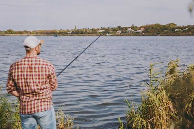 Widok z tyłu młody zarośnięty mężczyzna z wędką w kraciastej koszuli, czapce i okularach przeciwsłonecznych rzuca przynętę i wędkarstwo na jeziorze z brzegu w pobliżu krzewów i trzciny. styl życia, rekreacja, koncepcja wypoczynku rybaka.