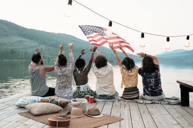 Widok z tyłu młodych ludzi siedzących na molo z amerykańską flagą i świętujących wakacje na łonie natury