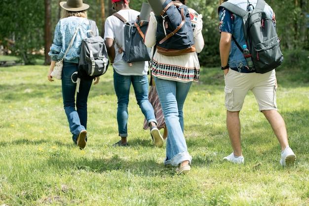 Widok z tyłu młodych turystów chodzących po trawie i noszących tornistry podczas wspólnej wędrówki
