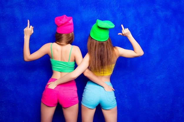 Widok z tyłu modnych kobiet pokazujących środkowy palec