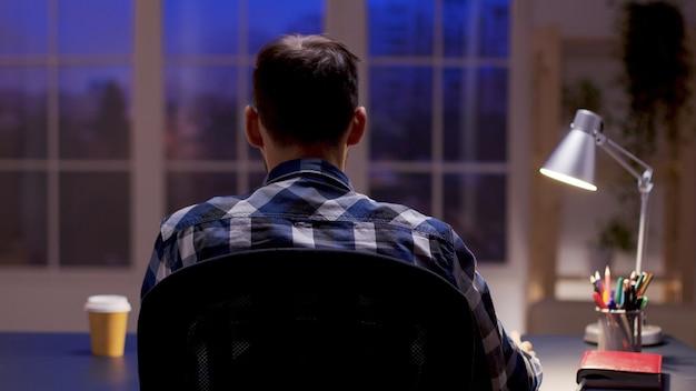 Widok z tyłu montażysty filmowego pracującego z domowego biura w godzinach nocnych.
