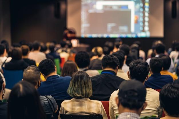 Widok z tyłu na azjatycką publiczność dołączającą i słuchającą mówcy przemawiającego na scenie podczas seminarium