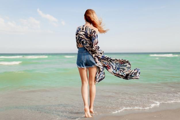 Widok z tyłu na beztroską, pełną wdzięku kobietę z niesamowitymi rudymi włosami biegnącą wzdłuż plaży