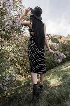 Widok z tyłu na elegancką brunetkę z eleganckimi długimi włosami w stylowym kapeluszu w modnej czarnej kobiecej sukience w skórzanych butach z kwiatami bzu w pobliżu kwitnących drzew w parku o zachodzie słońca. dziewczyna cieszy się majem.