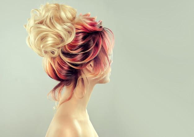 Widok z tyłu na elegancką, wielokolorową, pomalowaną fryzurę z dużym blond kokem. odcienie żółtego, czerwonego i czarnego koloru na pomalowanych włosach.