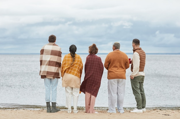 Widok z tyłu na grupę młodych ludzi na plaży jesienią owiniętych w koce kopia przestrzeń