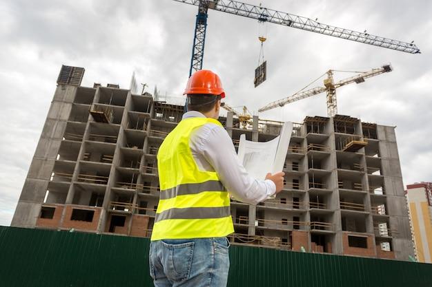 Widok z tyłu na inżyniera inspektora patrzącego na budynek w budowie
