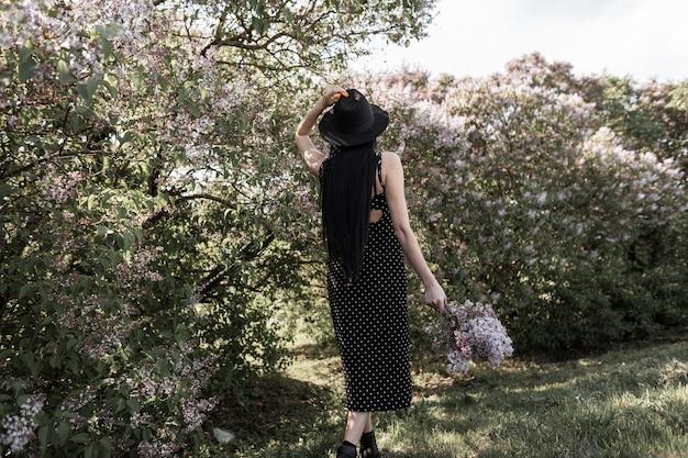 Widok z tyłu na kobietę z luksusowymi długimi włosami w modnej eleganckiej czarnej sukience z butami w stylowym kapeluszu iz bukietem pięknych kwiatów bzu. modna dziewczyna spacery w kwitnącym ogrodzie o zachodzie słońca.