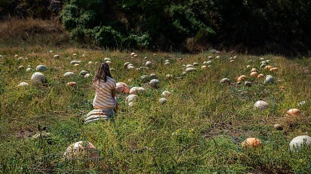 Widok z tyłu na kobietę z pomarańczową sukienką siedzi na ogromnej dyni w sadzie lato w tle z osobą