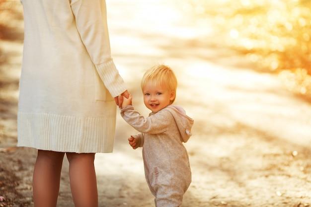 Widok z tyłu na ładny mały chłopiec maluch trzyma rękę matki i uśmiecha się. urocze dziecko spacery z mamą w parku w słoneczny letni dzień. rodzina na zachodzie słońca.