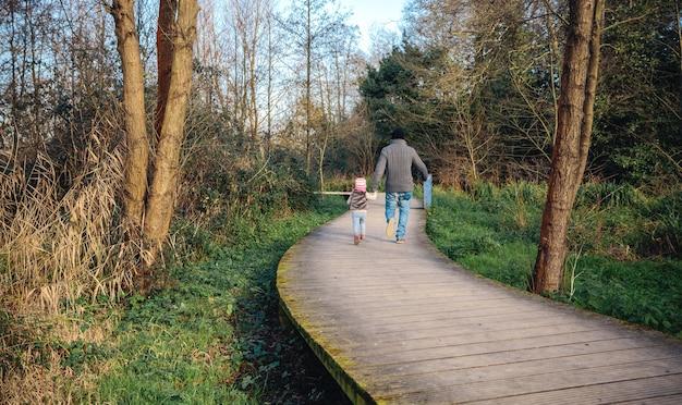 Widok z tyłu na mężczyznę i małą dziewczynkę trzymających się za ręce podczas chodzenia po drewnianej ścieżce do lasu