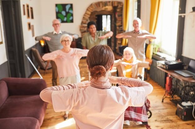Widok z tyłu na młodą kobietę koordynującą grupę starszych osób podczas porannych ćwiczeń, kopia przestrzeń