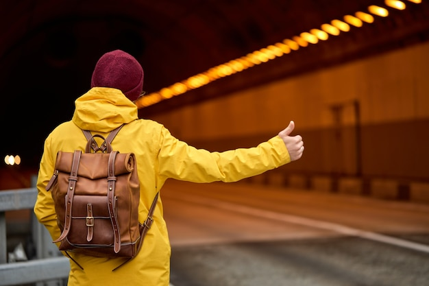 Widok z tyłu na młodego mężczyznę podróżującego autostopem po kraju, próbującego złapać przejeżdżający samochód