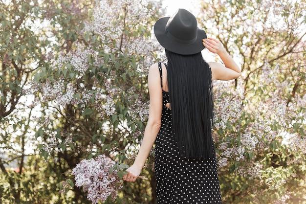 Widok z tyłu na modną kobietę z długimi włosami w stylowej sukience w modnym kapeluszu z bukietem kwiatów bzu w pobliżu kwitnącego drzewa w parku w słoneczny dzień. elegancka kobieca dziewczyna cieszy się pięknem natury.
