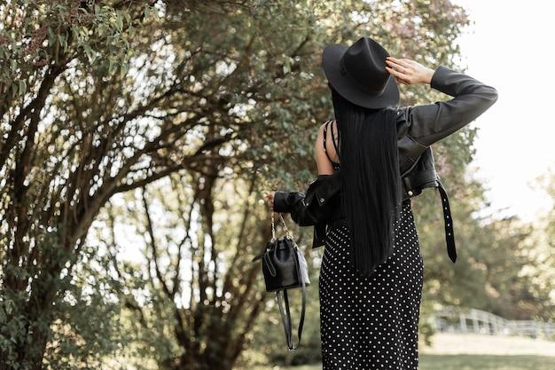 Widok z tyłu na modną kobietę ze zdrowymi długimi eleganckimi włosami w eleganckim czarnym kapeluszu w pięknej sukience w vintage kurtka ze skórzaną torebką w parku. modna dziewczyna w modzie czarne ubrania wiosna na spacer.