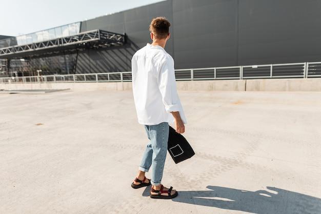 Widok z tyłu na modnego młodzieńca w stylowych ubraniach w czerwonych letnich butach z modną fryzurą z czarną torbą z tkaniny. współczesny facet spaceruje po mieście w jasny, słoneczny dzień. styl uliczny.