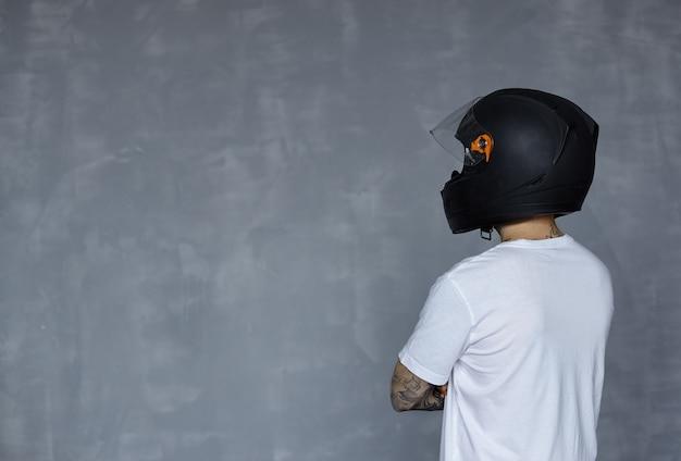 Widok z tyłu na motocyklistę w czarnym kasku i białej koszulce