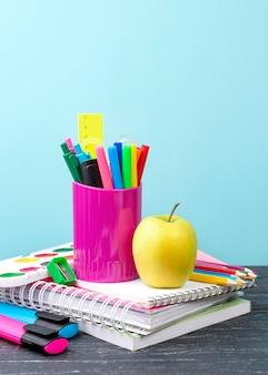 Widok z tyłu na przybory szkolne z jabłkiem i notatnikami