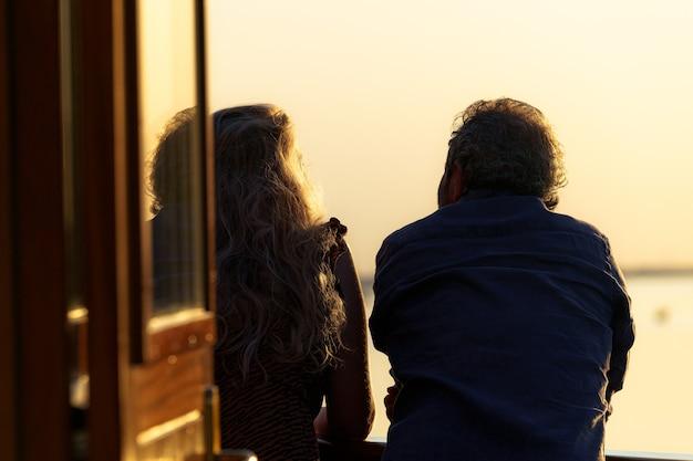 Widok z tyłu na romantyczną parę patrzącą na pokład łodzi podczas zachodu słońca