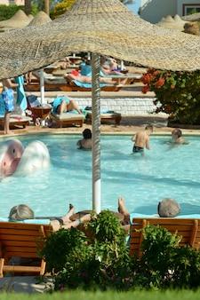 Widok z tyłu na starszą parę leżącą przy basenie w ośrodku hotelowym?