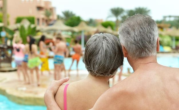 Widok z tyłu na starszą parę stojącą przy basenie w ośrodku hotelowym?