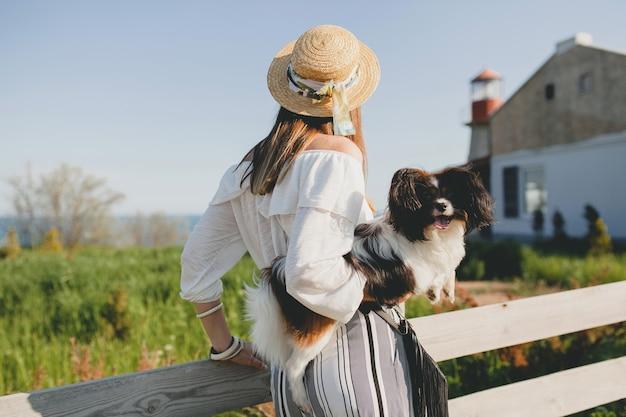 Widok z tyłu na stylową kobietę na wsi, trzymającą psa, szczęśliwy pozytywny nastrój, lato, słomkowy kapelusz, strój w stylu bohemy,