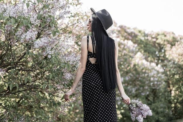 Widok z tyłu na zmysłową brunetkę z eleganckimi długimi włosami w stylowym kapeluszu w modnej czarnej sukience z kwiatami bzu w pobliżu kwitnących drzew w parku o zachodzie słońca. dziewczyna spaceruje i cieszy się niesamowitymi kwitnącymi drzewami