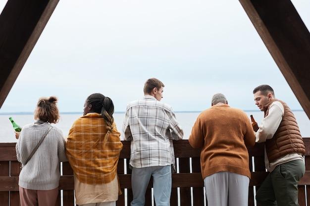 Widok z tyłu na zróżnicowaną grupę młodych ludzi relaksujących się na balkonie podczas imprezy w domu nad jeziorem