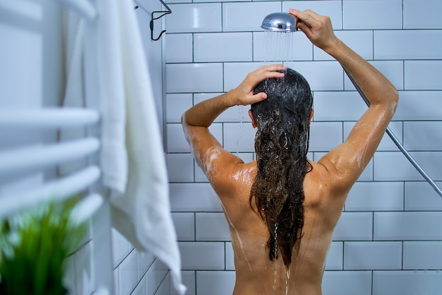 Widok z tyłu nagiej kobiety myjącej włosy szamponem pod prysznicem