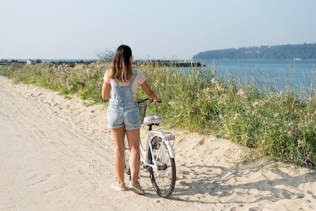 Widok z tyłu nastolatek z rowerem na zewnątrz