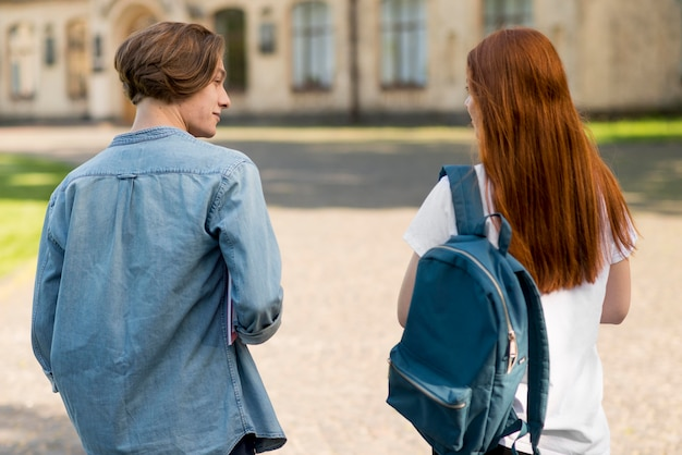Widok z tyłu nastolatków chodzących razem w kampusie