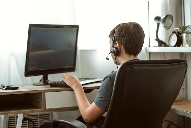 Widok z tyłu nastoletniego chłopca grającego w gry online