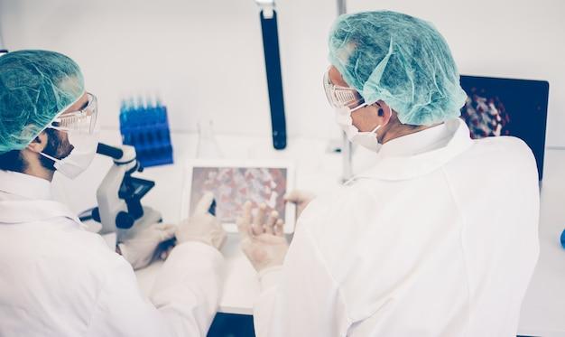 Widok z tyłu. naukowcy omawiają nowe informacje na temat rozwoju wirusa. pojęcie zdrowia.