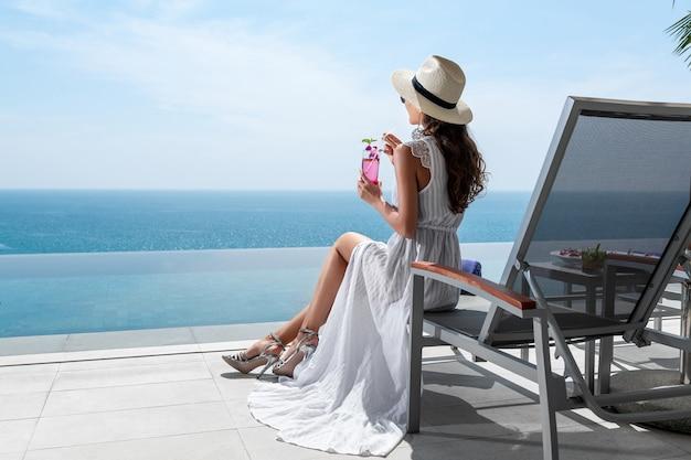 Widok z tyłu: nie do poznania dziewczyna w białej sukni cieszy się wakacjami na leżaku i pije koktajl