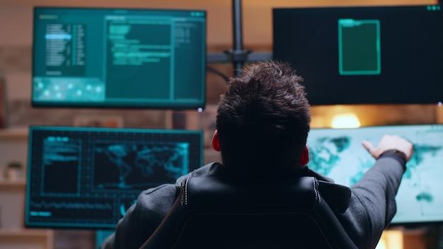 Widok z tyłu niebezpieczne i poszukiwane cyberprzestępcy przeszukujący rządową bazę danych.