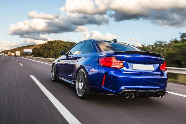 Widok z tyłu niebieski sedan na drodze.