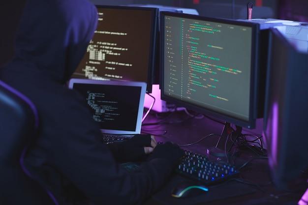 Widok z tyłu nierozpoznawalnego hakera cyberbezpieczeństwa noszącego kaptur podczas pracy nad programowaniem kodu w ciemnym pokoju, miejsce na kopię