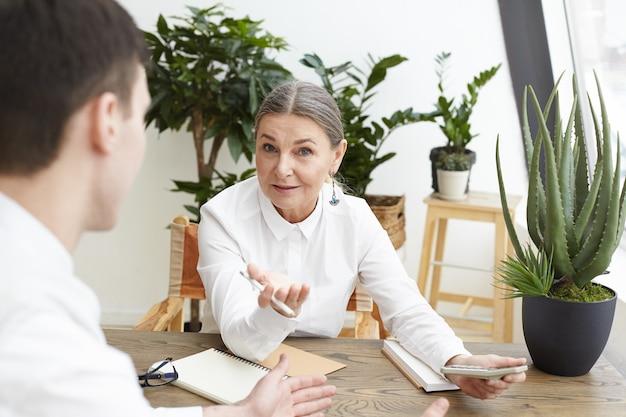 Widok z tyłu nierozpoznawalnego młodego kandydata płci męskiej odbywającej rozmowę kwalifikacyjną z pewną siebie siwowłosą kobietą w średnim wieku, która trzyma ołówek i kalkulator, mówiąc mu o pożądanej pozycji