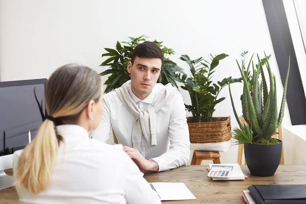 Widok z tyłu nierozpoznawalnej kobiety w średnim wieku ubiegającej się o pracę z siwymi włosami siedzącej przed przystojnym, pewnym, młodym męskim pracodawcą podczas rozmowy kwalifikacyjnej. ludzie, biznes, zawód i kariera