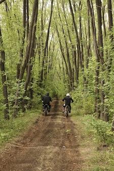 Widok z tyłu nierozpoznawalnych motocyklistów w kaskach pędzących leśną drogą między długimi drzewami