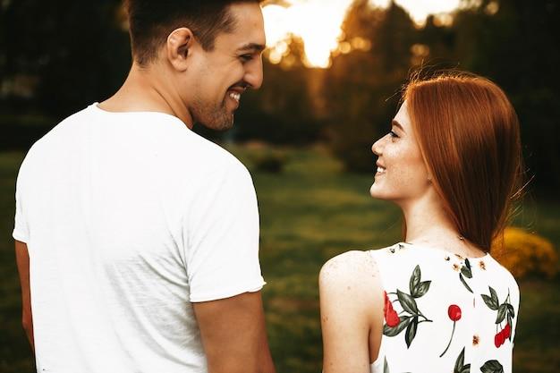 Widok z tyłu niesamowitej pary trzymającej się za rękę i patrząc na siebie, śmiejąc się przed zachodem słońca podczas randkowania na zewnątrz.