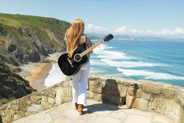 Widok Z Tyłu Nieznanej Gitarzystki Patrzącej Na Morze Z Czarną Gitarą Na Plecach, Ona Wstaje Premium Zdjęcia