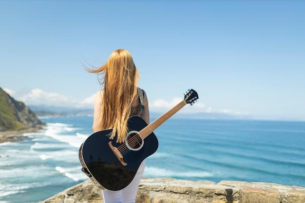 Widok z tyłu nieznanej gitarzystki patrzącej na morze z czarną gitarą na plecach, ona wstaje