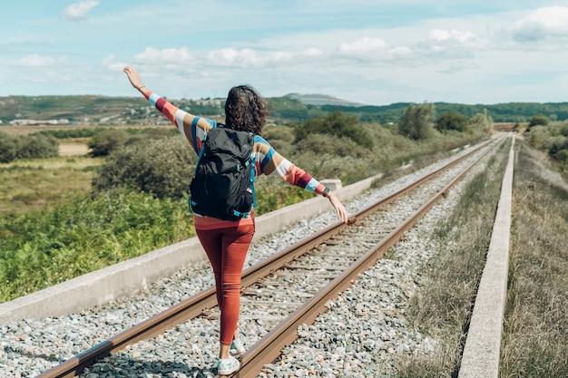 Widok z tyłu nieznanej podróżniczki idącej wzdłuż linii kolejowych.
