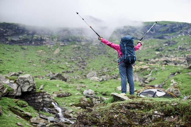 Widok z tyłu niski kąt ujęcia kobiety wycieczkowicza z plecakiem rozkładającym ramiona kijkami trekkingowymi